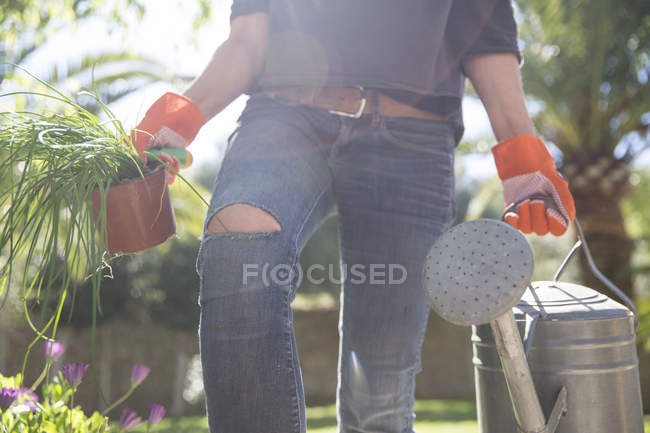 Woman carrying plant and watering can in garden — Stock Photo