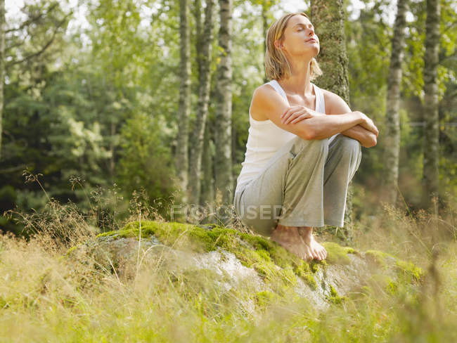 Woman crouching on a large rock — Stock Photo
