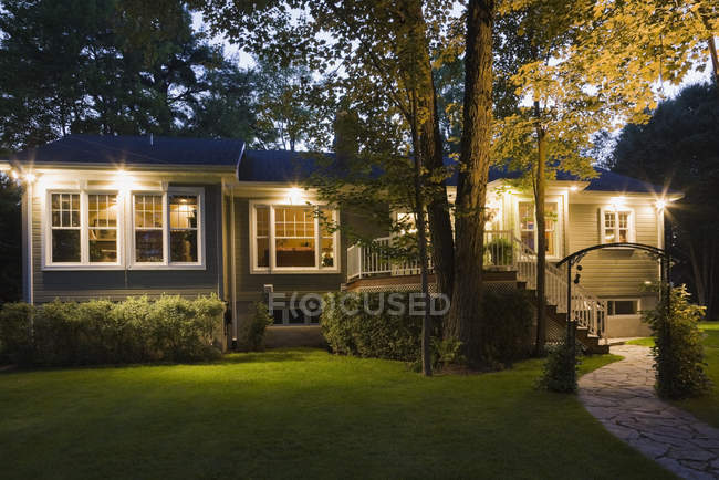 Residential house facade with lights at dusk — Stock Photo