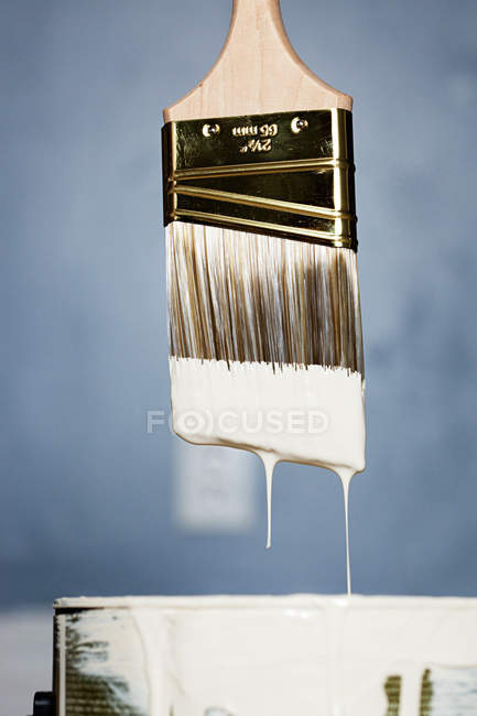 Paintbrush with white paint dripping in can, close up shot — Stock Photo