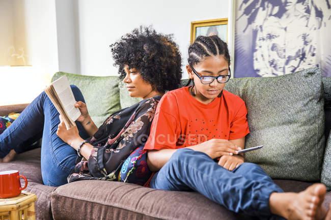 Зрелая женщина и сын спина к спине на гостиной диван — стоковое фото