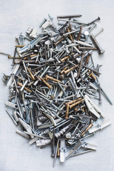Top view of Nails and screws on grey surface — Stock Photo