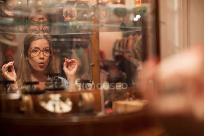 Giovane donna cercando gli occhiali e che tira i fronti in negozio vintage — Foto stock
