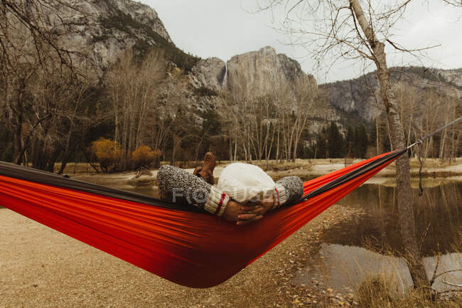 Rear view of woman reclining in red hammock looking out at landscape, Yosemite National Park, California, USA — Fotografia de Stock