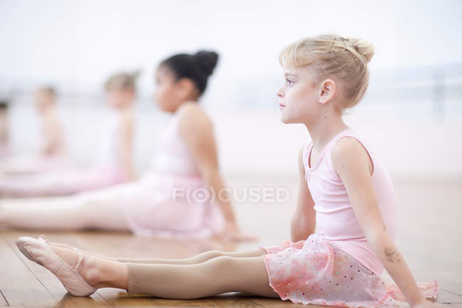 Young ballerinas sitting on floor in pose — Stock Photo