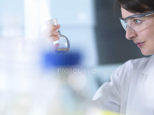 Scientist viewing chemical formula in beaker during  experiment in laboratory — Stock Photo