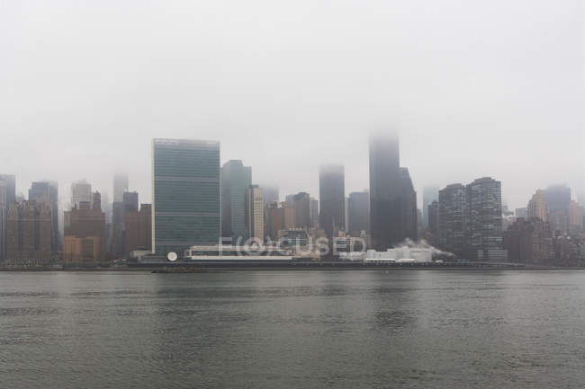 Puerto y rascacielos cubiertos de nubes de baja niebla - foto de stock