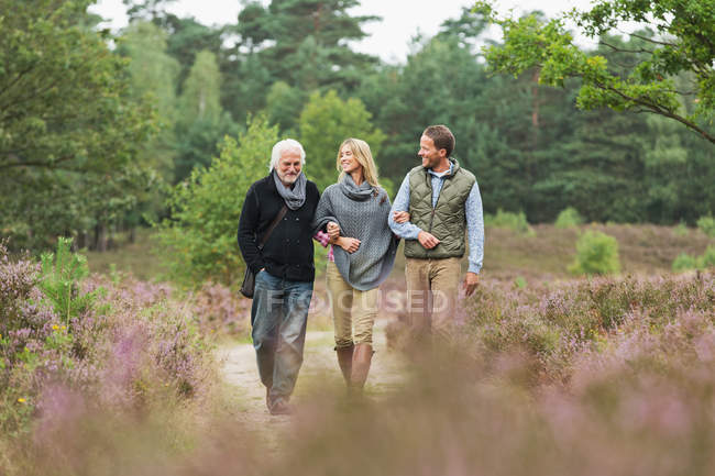 Senior man, mid adult man and woman walking through forest — Stock Photo