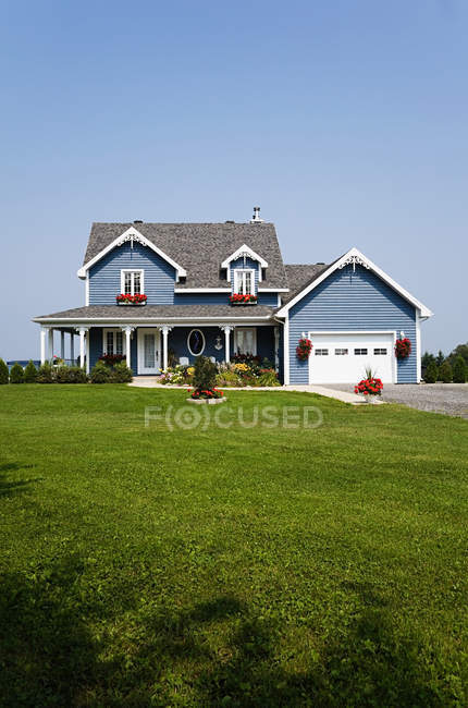 Blue house and green lawn under clear sky — Stock Photo