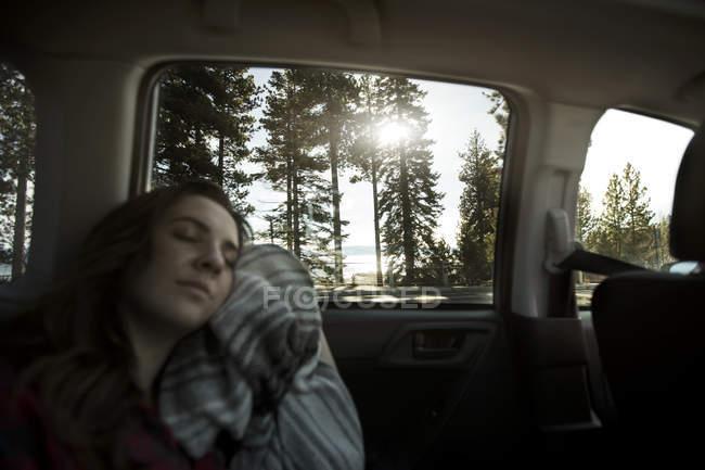 Teenage girl sleeping in back seat of car — Stock Photo