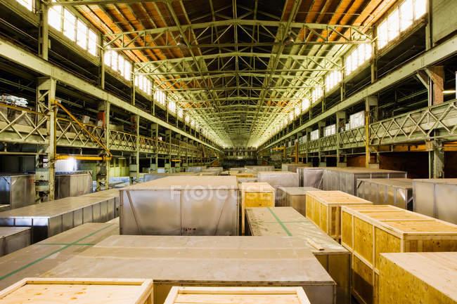 Caisses dans un entrepôt de distribution éclairé, perspective décroissante — Photo de stock
