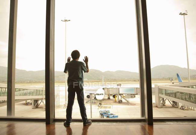 Garçon regardant hors de la fenêtre d'aéroport — Photo de stock