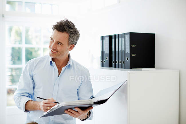 Man holding folder of paperwork in office — Stock Photo