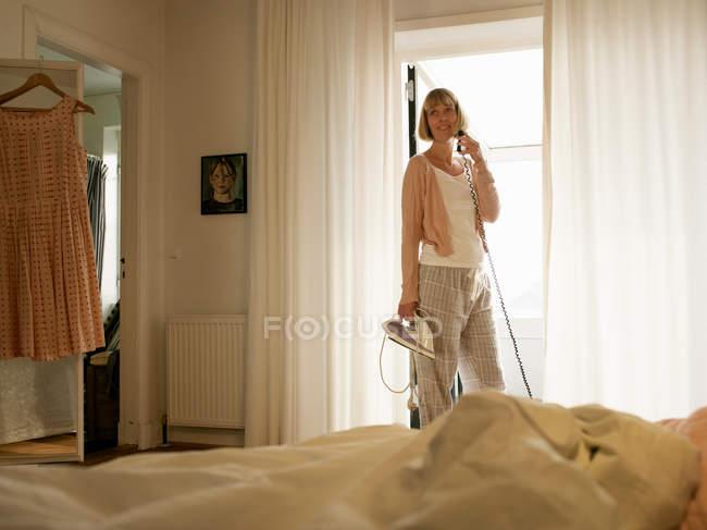 Femme mûre tenant fer et faire un appel téléphonique dans la chambre — Photo de stock