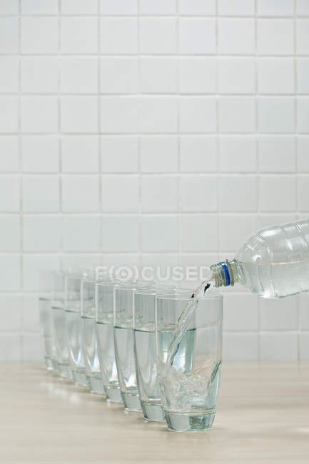 Mineral water pouring in glasses from bottle — Stock Photo