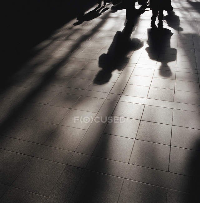 Shadows of people on street pavement — Stock Photo