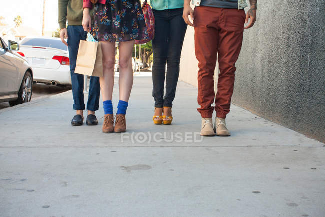 Stylish four people standing on pavement, low section — Stock Photo