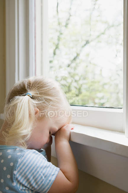 Sad little girl by window — Stock Photo