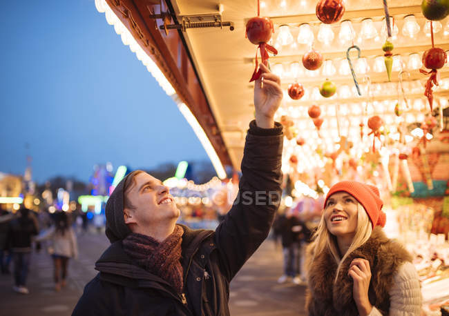 Young couple choosing baubles at xmas festival in Hyde Park, London, UK — Stock Photo