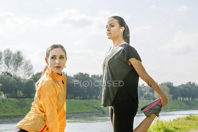 Two female friends exercising outdoors, stretching — Stock Photo