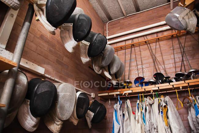 Esgrima máscaras e folhas penduradas na parede — Fotografia de Stock