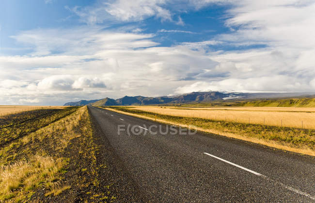 Rural road under cloudy sky — Stock Photo