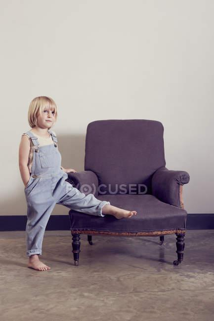 Девушка в балаклавах с поднятой ногой на винтажном кресле — стоковое фото