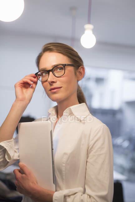 Affidabile donna d'affari guardando lateralmente mentre si utilizza tablet digitale in ufficio — Foto stock