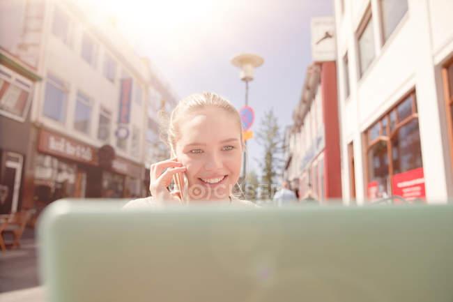 Adolescente sentada al aire libre usando computadora portátil, hablando por teléfono celular, Reykjavik, Islandia - foto de stock