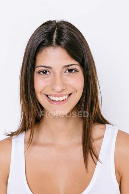 Ritratto di giovane donna che indossa la maglia bianca guardando sorridere della macchina fotografica — Foto stock