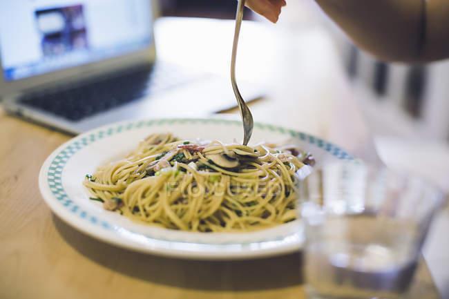 Молодая женщина на таблице еды тарелку лапши, фокус на продовольствие — стоковое фото