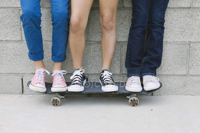 Three girls standing on skateboard, low section — Stock Photo