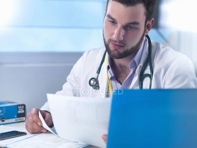 Médico junior leyendo historias clínicas en la clínica - foto de stock
