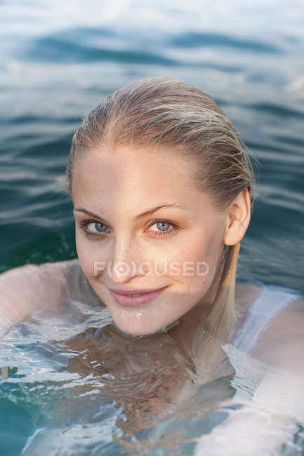 Close up portrait of young woman in lake — Stock Photo