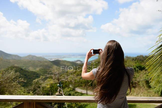 Вид сзади женщина принимая картину пейзаж побережья — стоковое фото