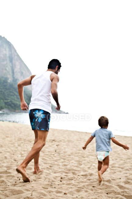Père et fils en jouant sur la plage — Photo de stock
