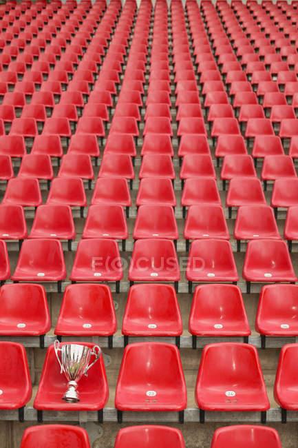 Trofeo en el asiento del estadio de fútbol vacío - foto de stock