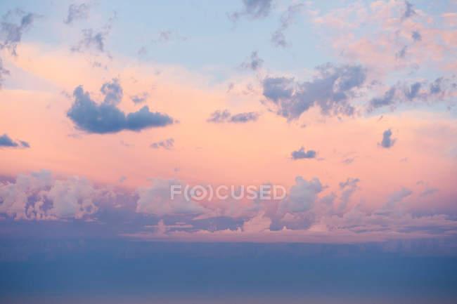 Cloudscape em cores rosa e roxas quentes durante o pôr do sol — Fotografia de Stock