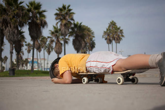 Boy laying on skateboard in park — Stock Photo