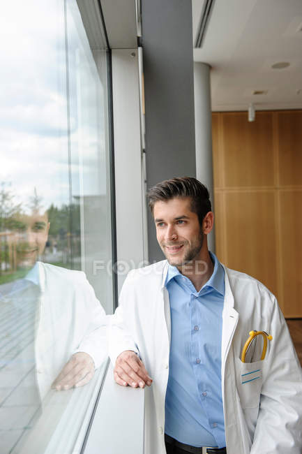 Portrait of young male doctor smiling and standing at the window — Stock Photo