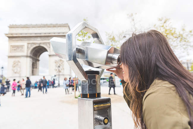 Young woman looking through coin binoculars at Arc de Triomphe, Paris, France — Stock Photo