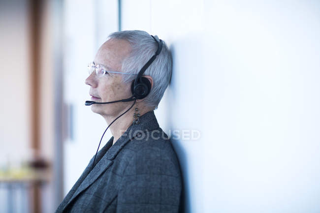 Side view of mature woman leaning against wall wearing telephone headset looking away — Stock Photo