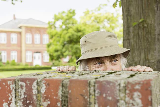 Старший мужчина, носить шляпу вглядываясь через стены сада — стоковое фото