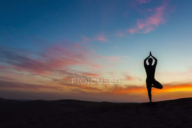 Silhouette Of Mid Adult Man On One Leg Arms Raised Doing Yoga Pose Against