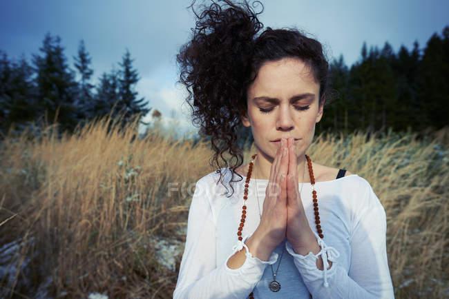 Mulher adulta média meditando na floresta — Fotografia de Stock