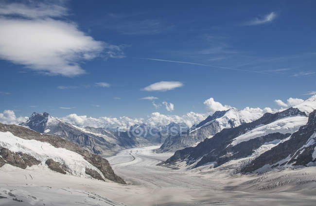 Snowcapped valley and mountains under blue cloudy sky — Stock Photo