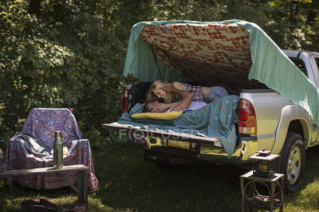 Young woman kissing boyfriend in pick up boot whilst camping — Stock Photo
