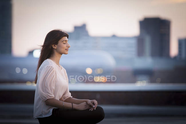 Vista lateral da mulher meditando no telhado — Fotografia de Stock