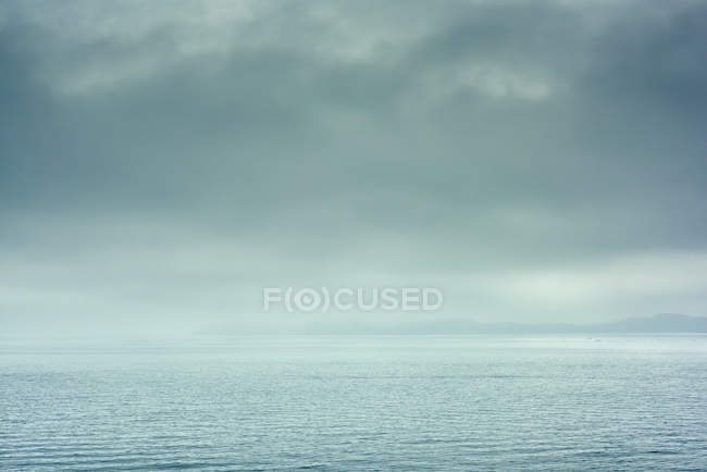 Horizon over calm water with dramatic cloudy sky — Stock Photo