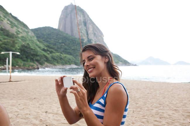 Woman using camera phone on beach, Rio de Janeiro, Brazil — Stock Photo